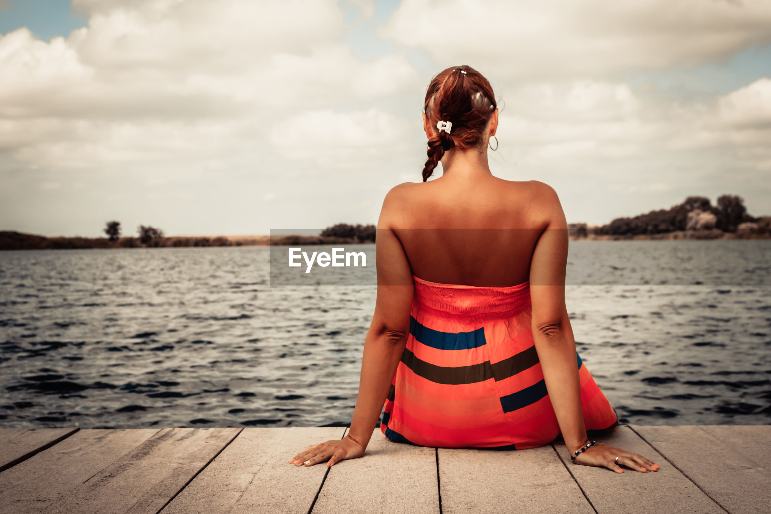 Rear view of woman relaxing on a pier while spending summer day at the beach.