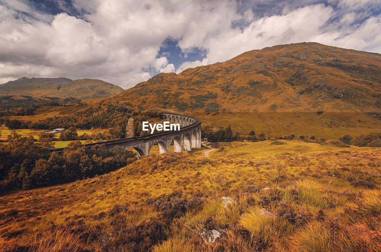 Bridge Over Field Against Cloudy Sky At Glenfinnan