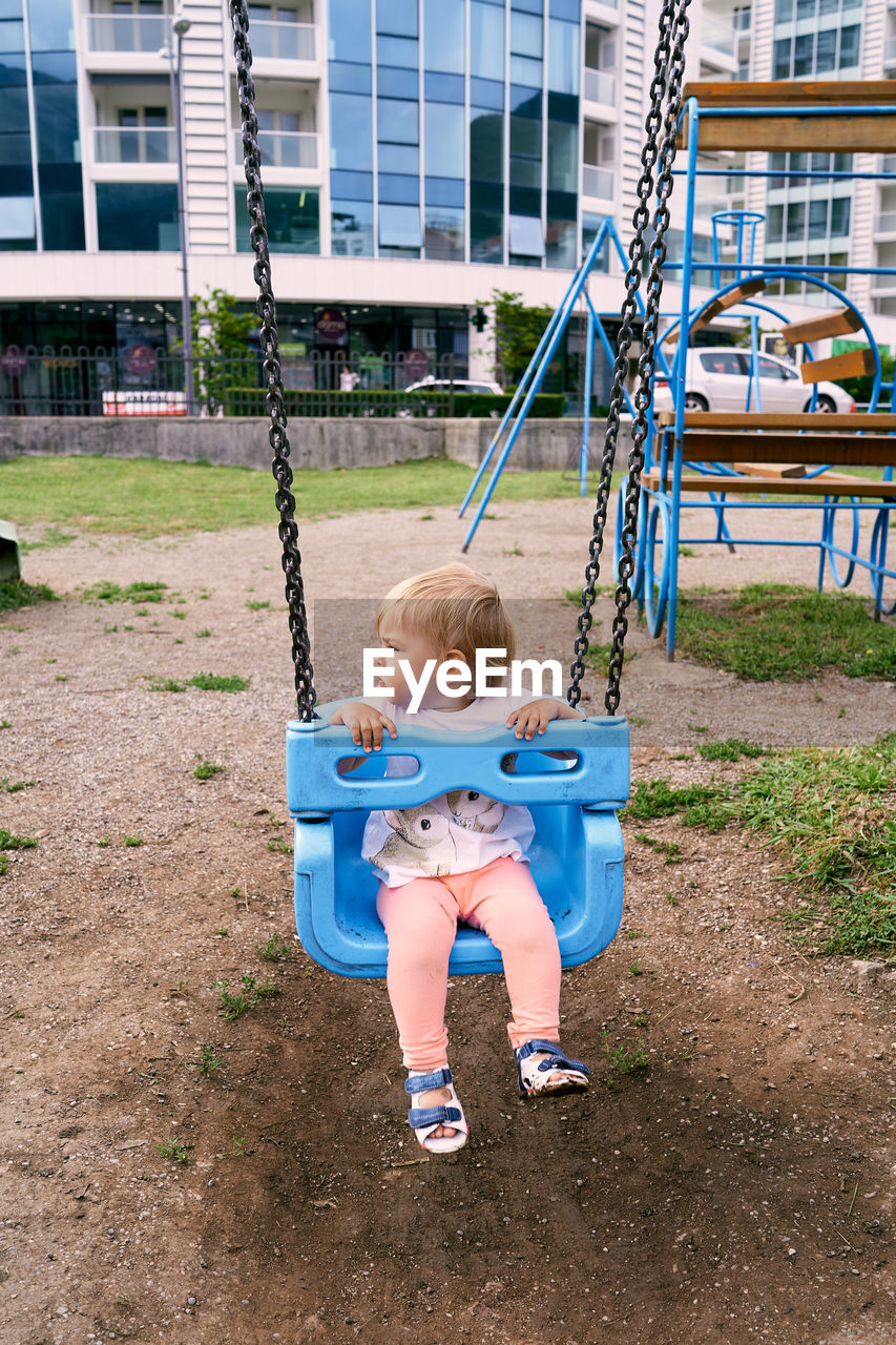 FULL LENGTH OF BOY PLAYING ON SWING
