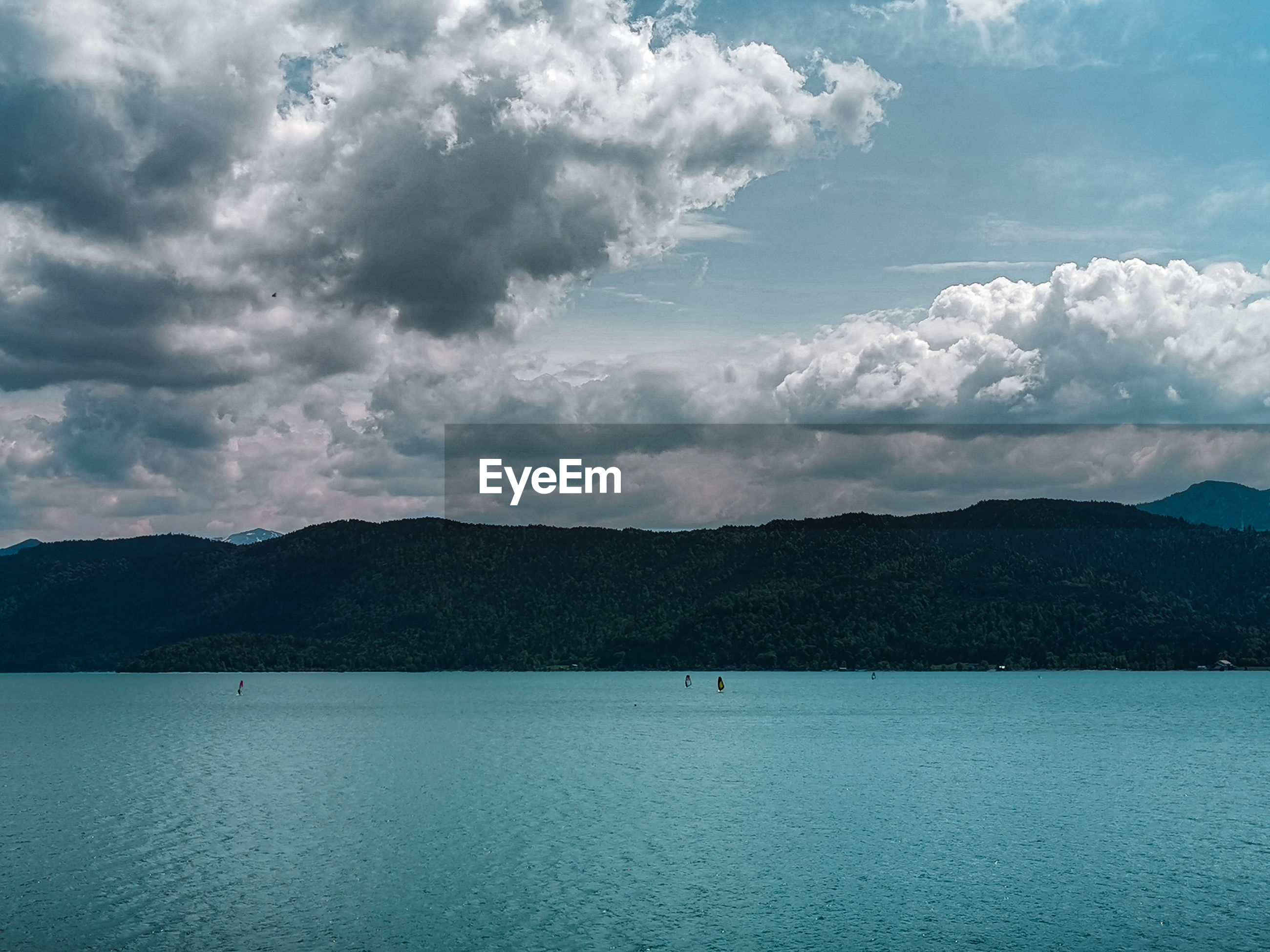 Upcoming clouds over lake walchensee and mountains, with kiters on the lake, bavaria, germany