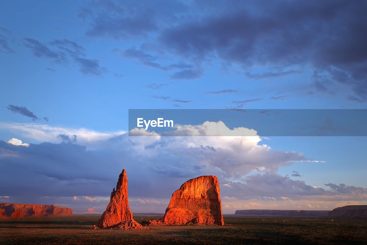 Scenic view of rock formations on field against cloudy sky