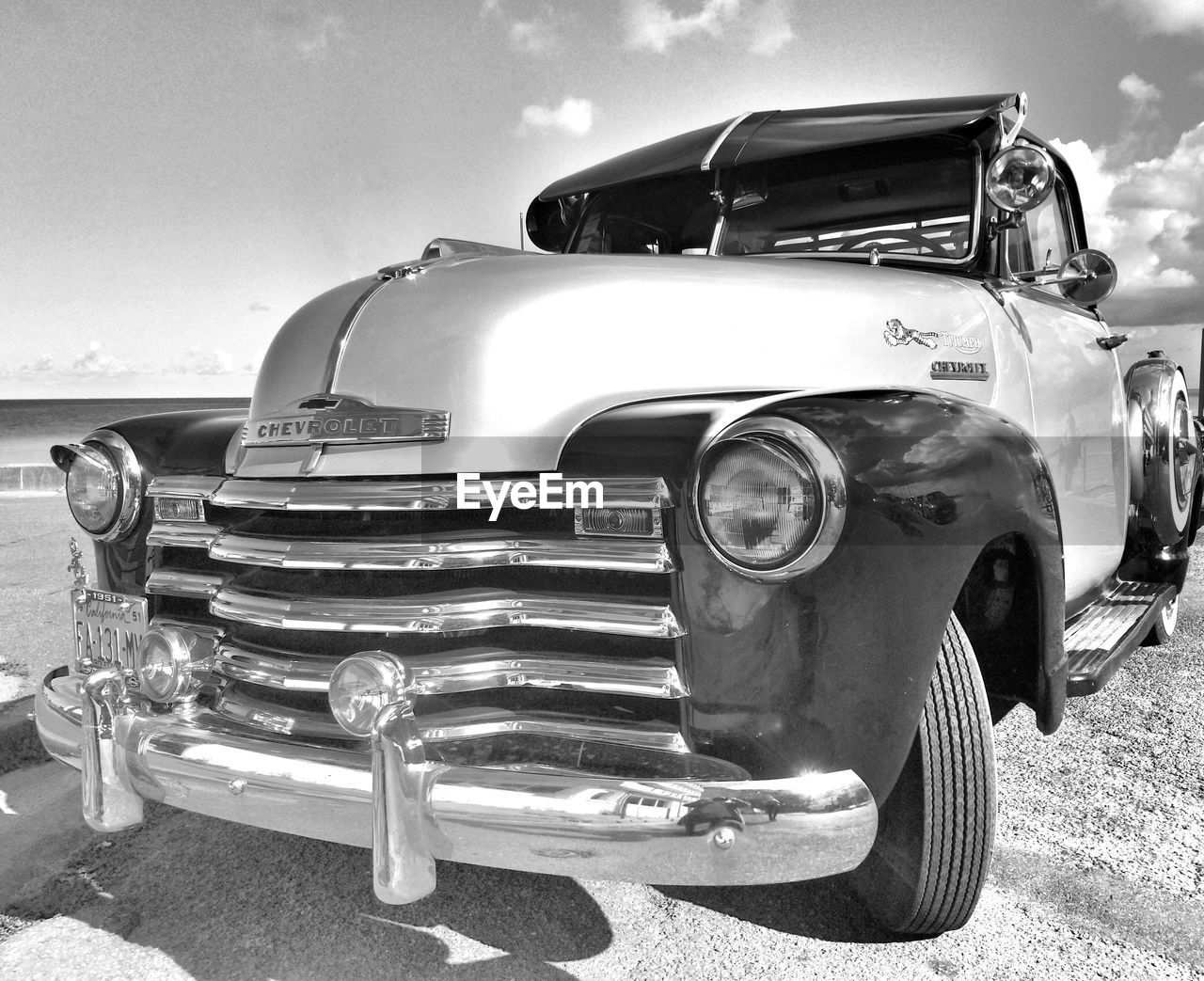 mode of transportation, land vehicle, transportation, car, retro styled, motor vehicle, headlight, day, vintage car, sky, metal, no people, nature, stationary, front view, outdoors, sunlight, antique, cloud - sky, luxury, chrome