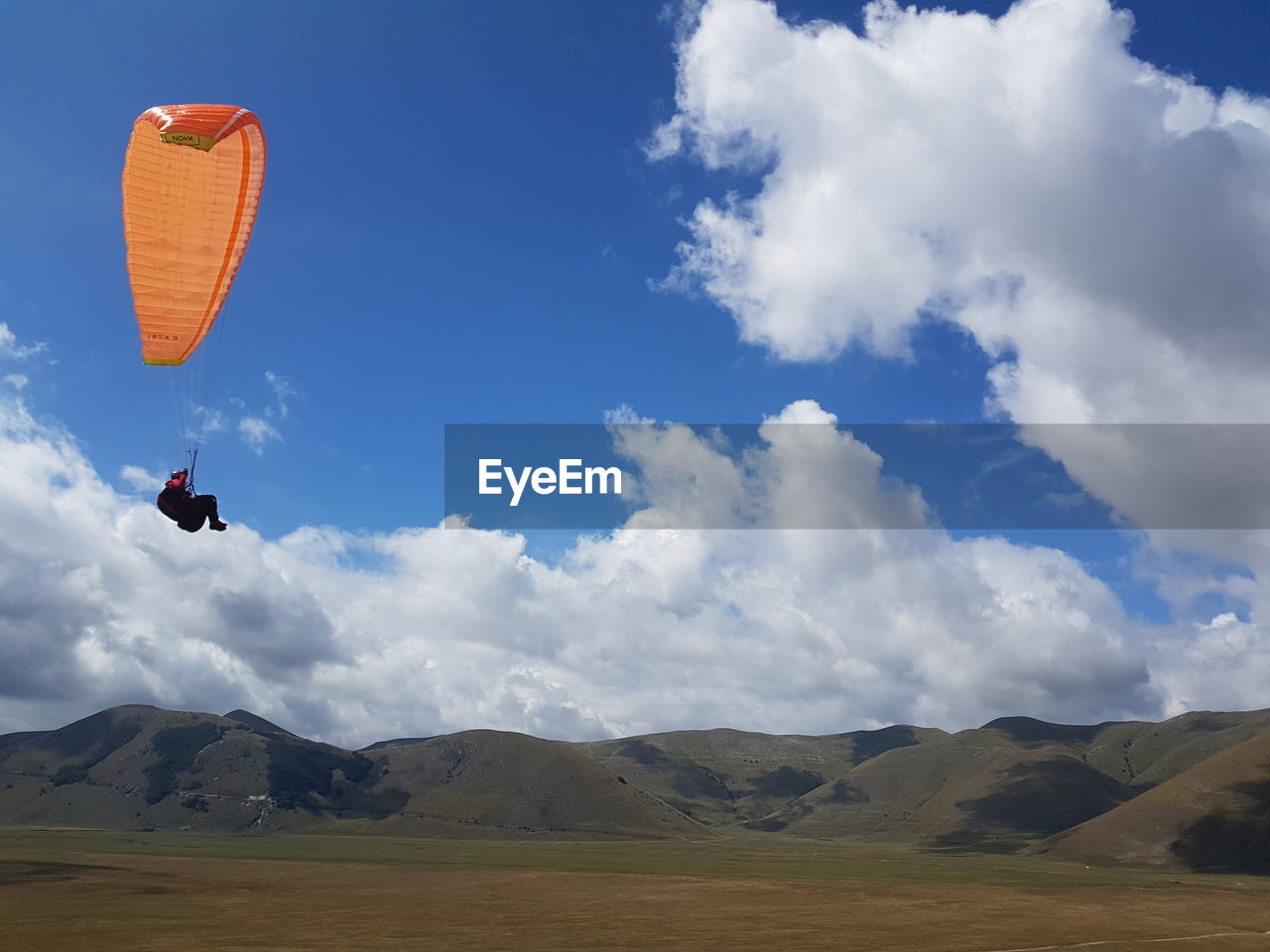 sky, cloud - sky, adventure, sport, mountain, extreme sports, leisure activity, beauty in nature, one person, mid-air, nature, scenics - nature, day, real people, parachute, lifestyles, unrecognizable person, flying, paragliding, outdoors