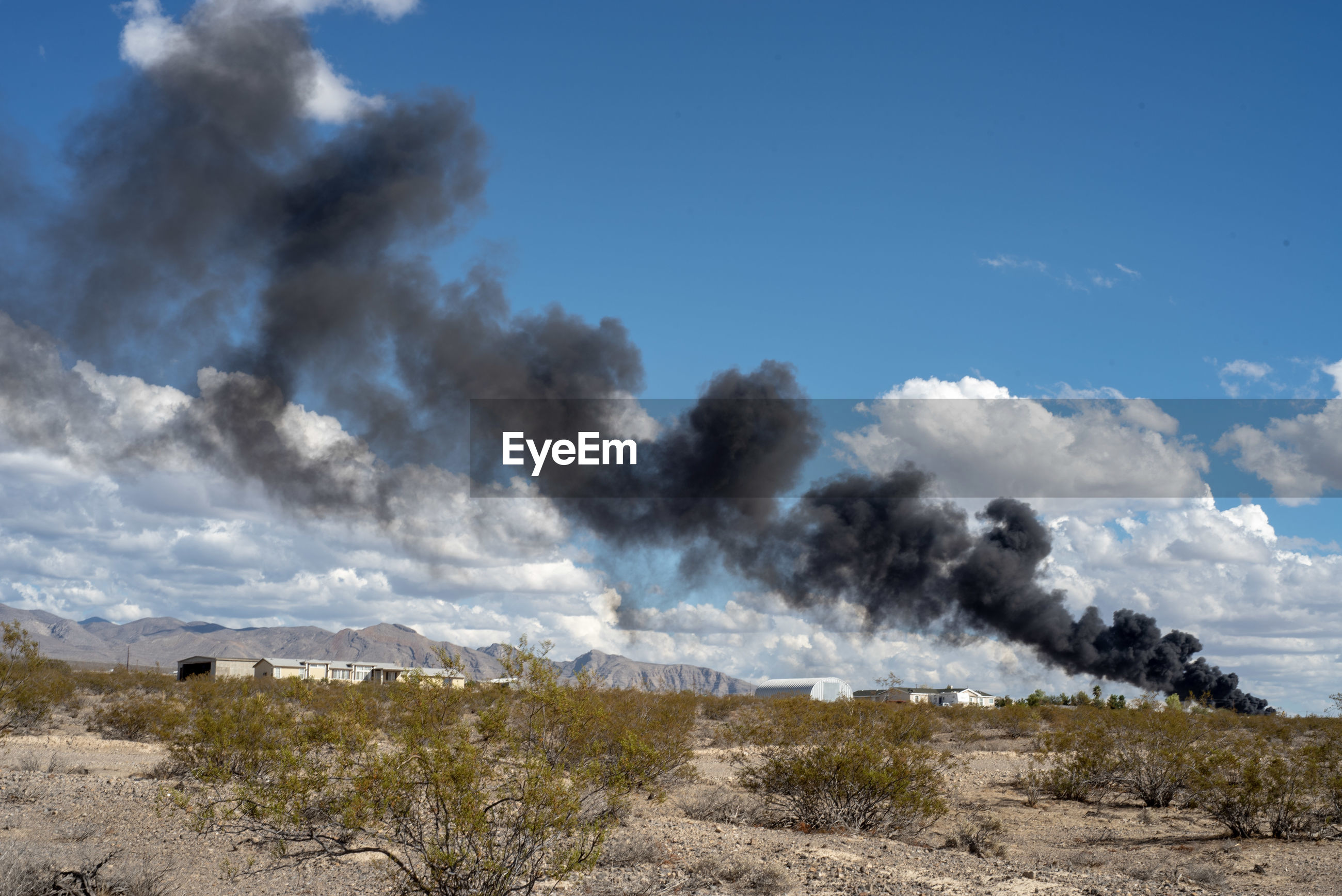Smoke over landscape against sky
