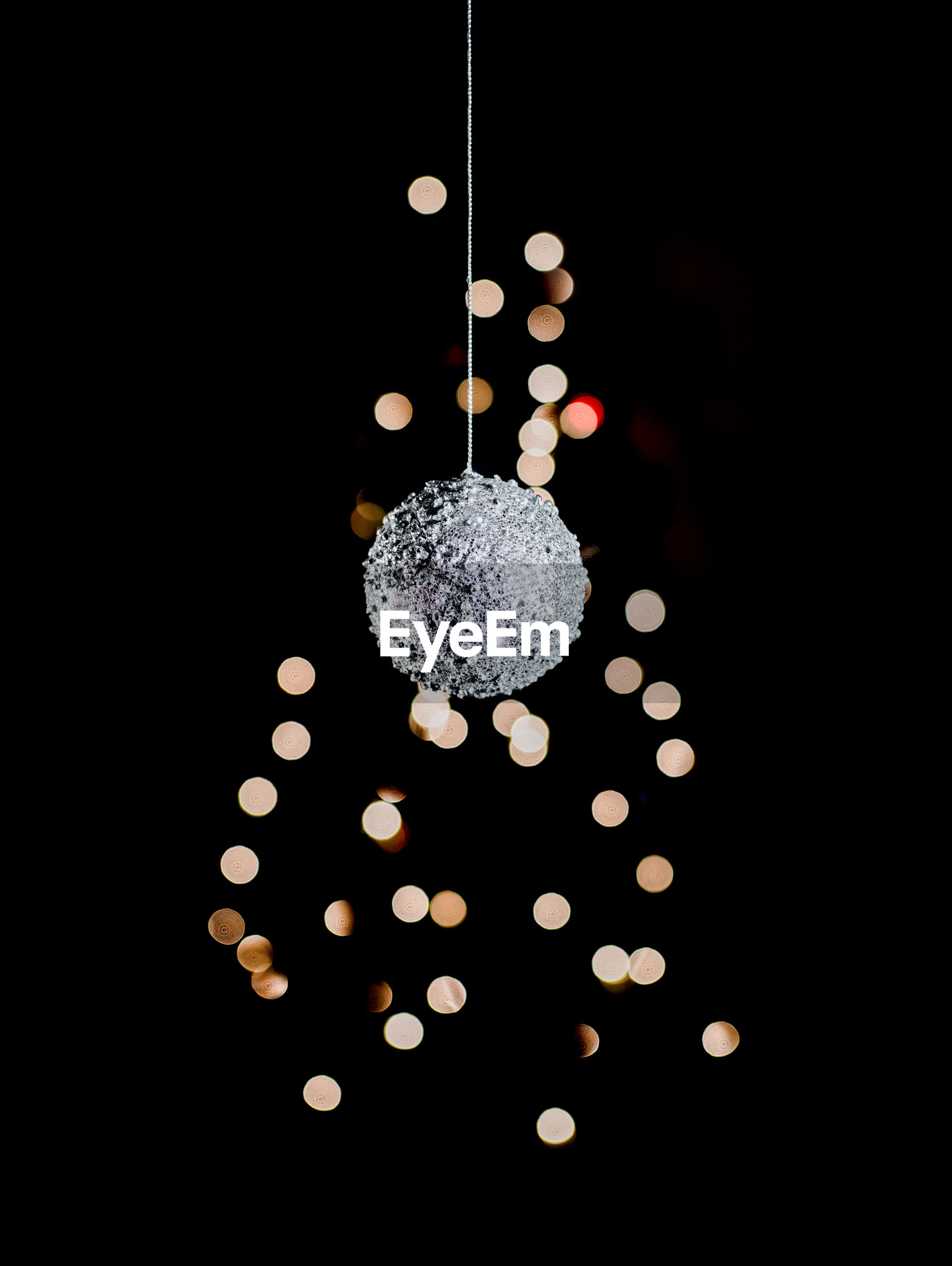 Christmas ornament and lights against black background