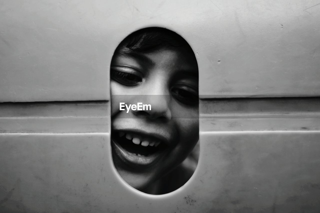 Portrait of smiling boy looking through hole