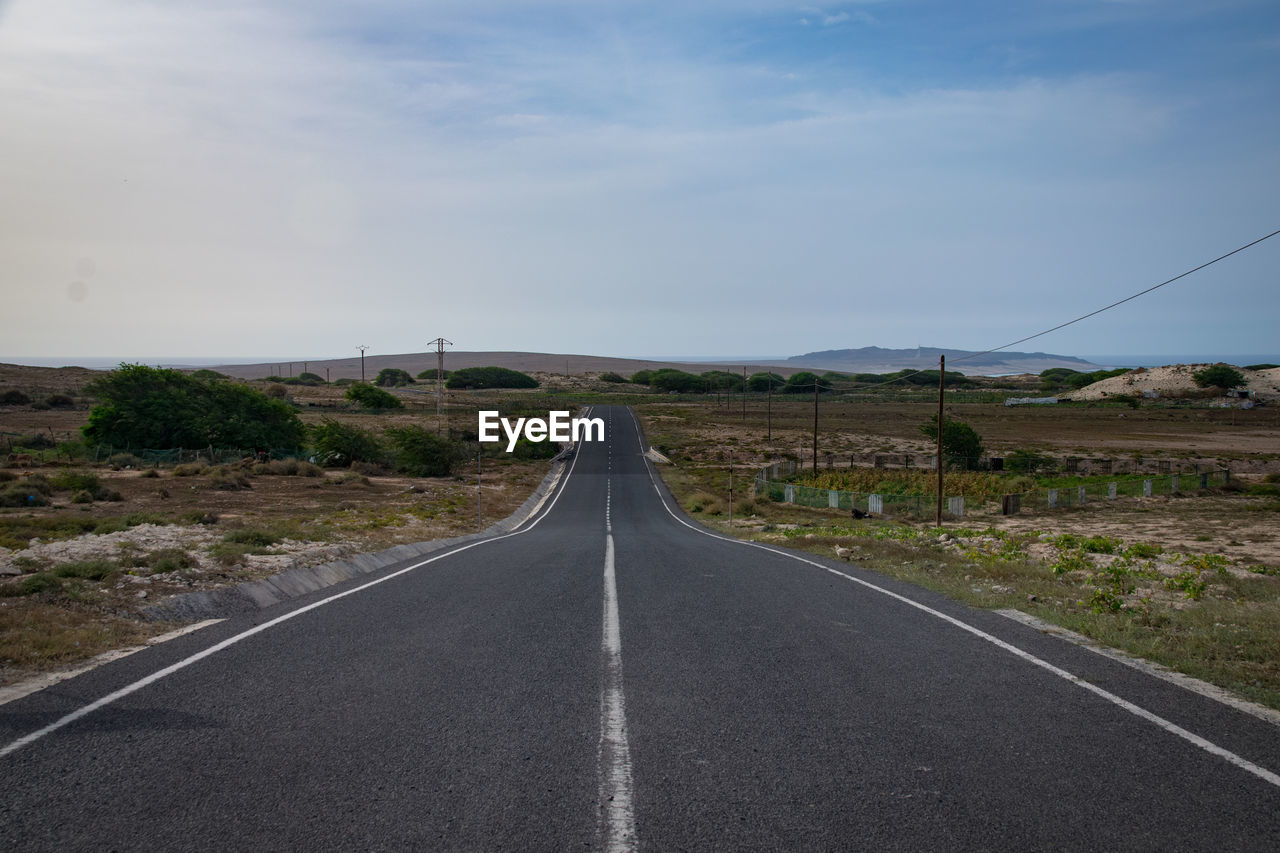 road, transportation, direction, the way forward, sky, sign, road marking, marking, diminishing perspective, symbol, nature, vanishing point, no people, landscape, day, environment, empty road, tranquil scene, connection, country, outdoors, dividing line