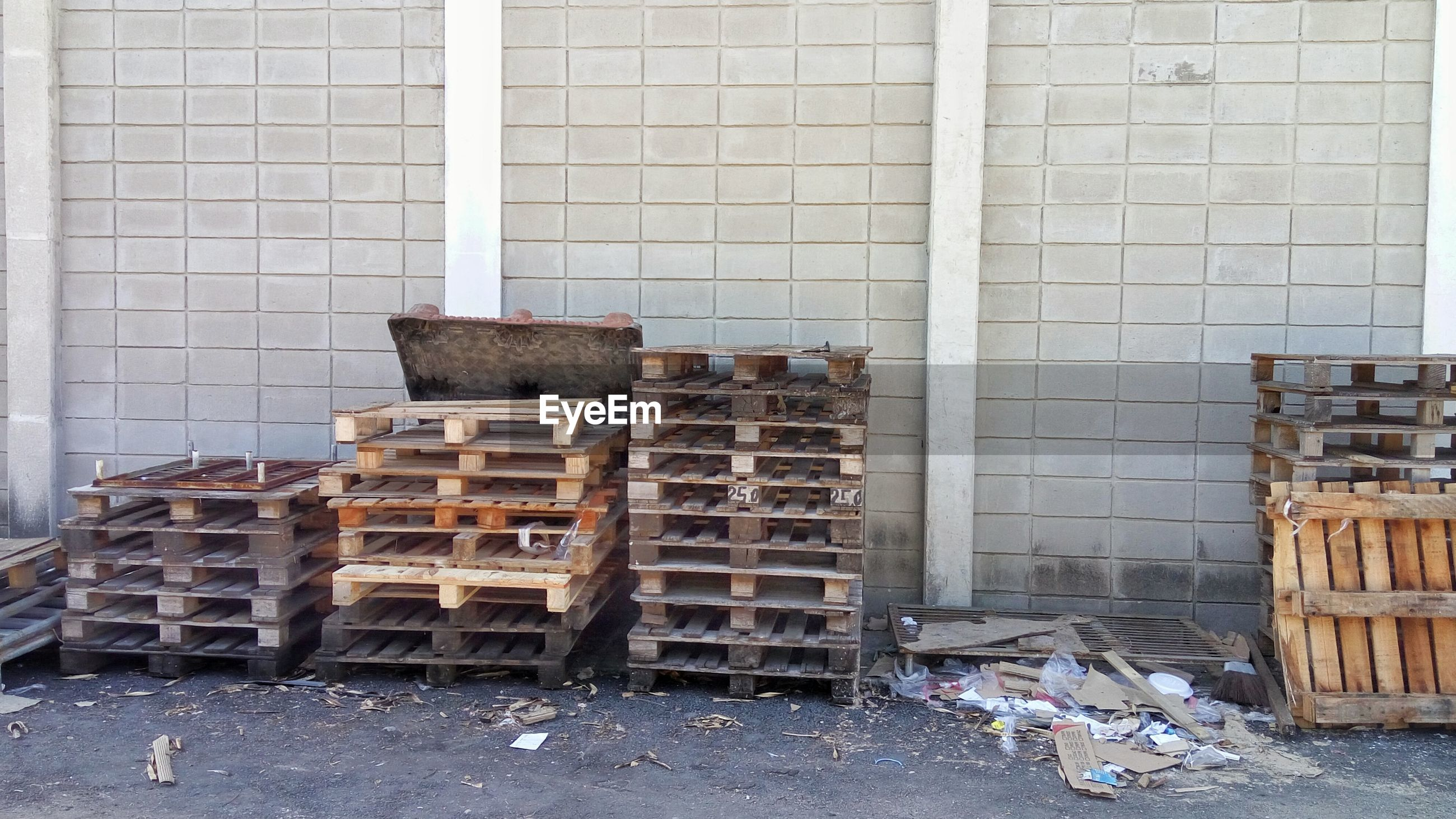 Wooden pallets on footpath against wall