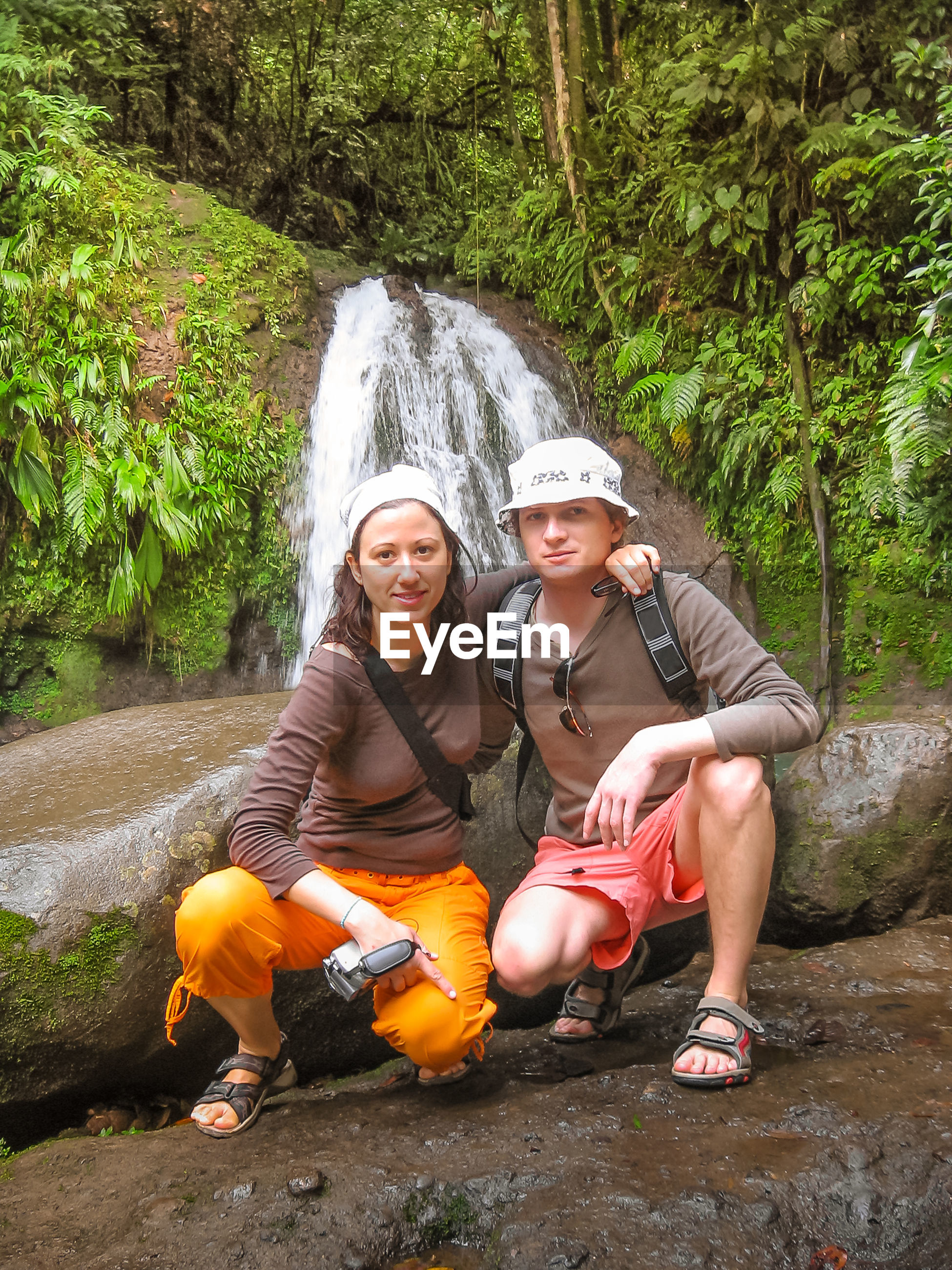 Portrait of couple crouching against waterfall