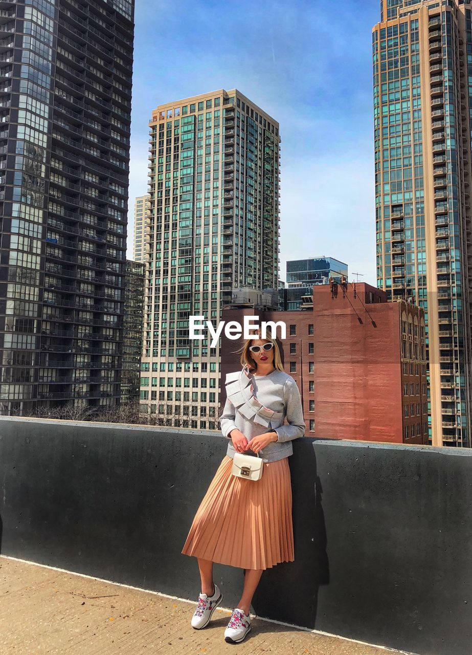 architecture, built structure, building exterior, one person, young adult, looking at camera, building, real people, city, young women, lifestyles, leisure activity, women, portrait, casual clothing, day, adult, full length, sky, office building exterior, fashion, outdoors, beautiful woman, skyscraper, modern, hairstyle
