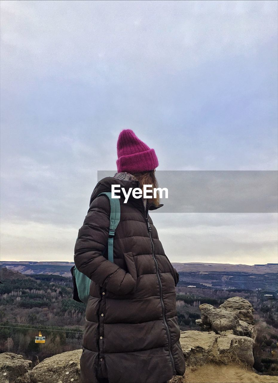 Woman wearing warm clothing while looking at view against sky during winter