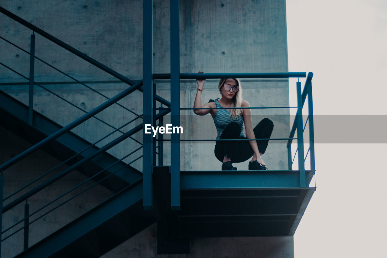 Low Angle View Of Woman Crouching On Staircase