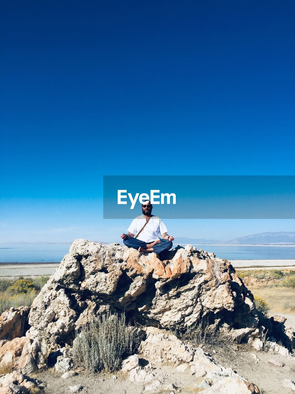 sky, one person, real people, lifestyles, rock, rock - object, leisure activity, blue, solid, clear sky, beauty in nature, sunlight, nature, scenics - nature, tranquility, young adult, day, sitting, copy space, outdoors