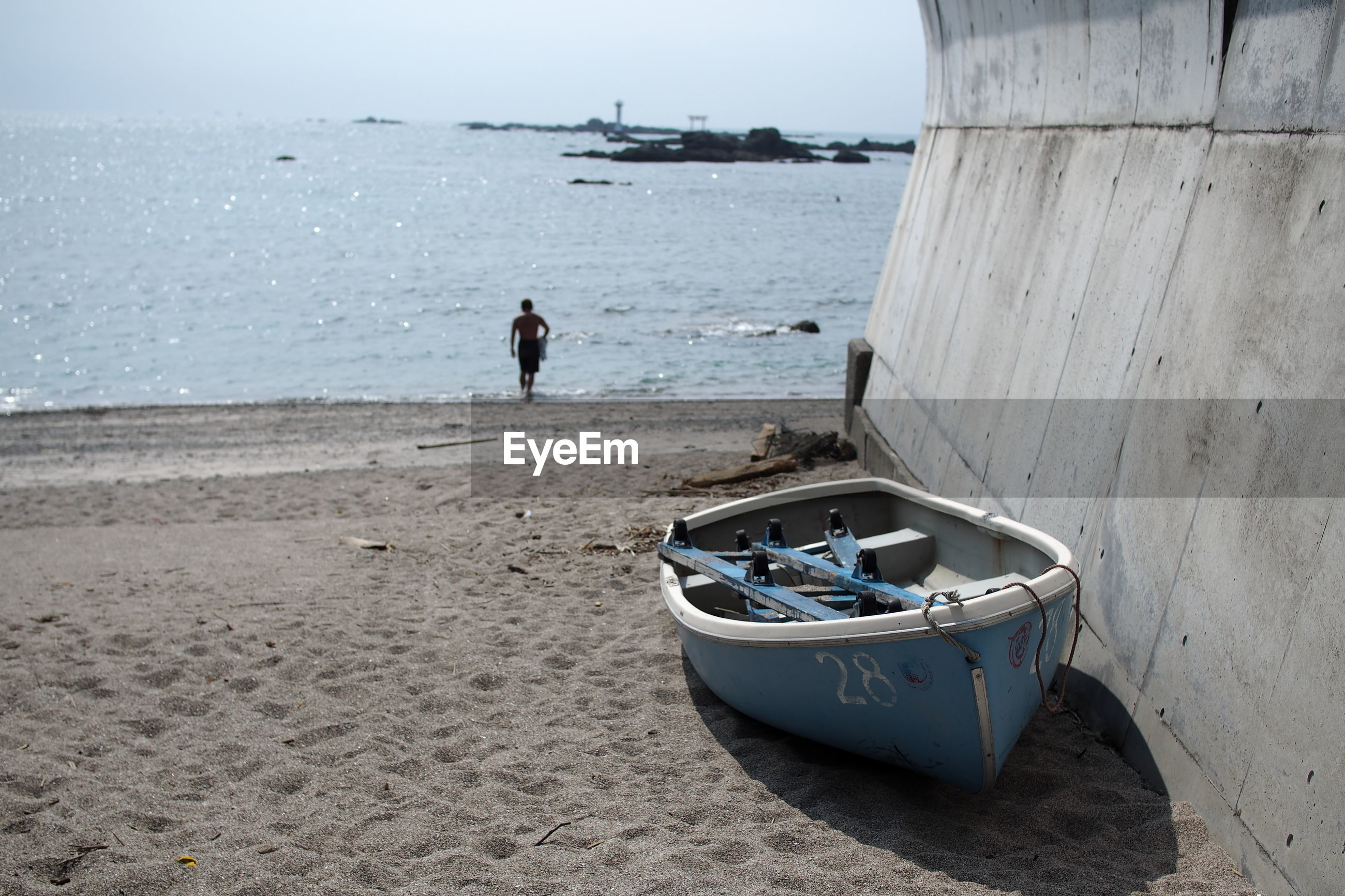 Moored boat with shirtless man walking at beach by sea against sky