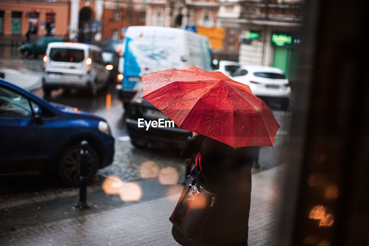 Person With Red Umbrella Standing On Sidewalk During Rainy Season In City
