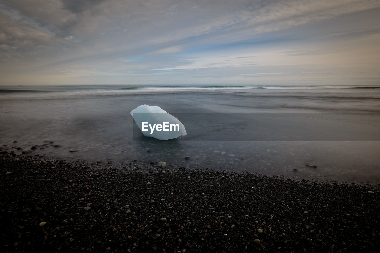 ice, sea, nature, beauty in nature, water, tranquility, sky, tranquil scene, cold temperature, beach, glacier, iceberg - ice formation, iceberg, scenics, horizon over water, sunset, melting, floating on water, frozen, outdoors, sand, winter, no people, day