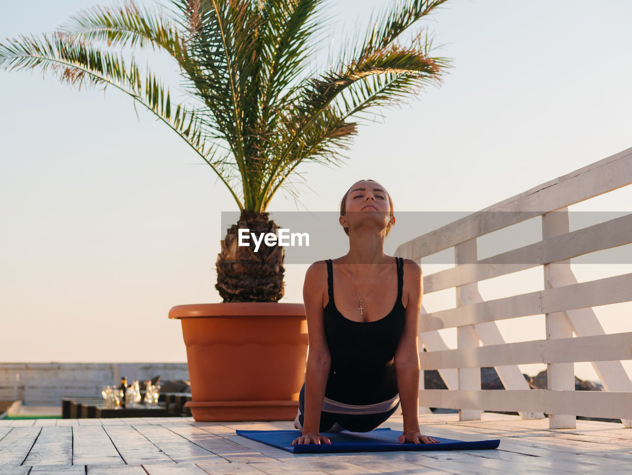 Woman With Closed Eyes Doing Yoga On Promenade Against Clear Sky During Sunrise