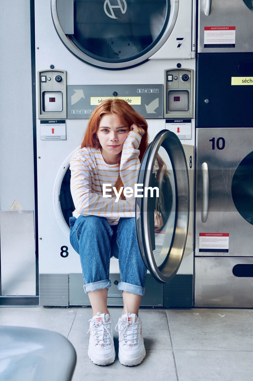 one person, machinery, washing machine, indoors, full length, appliance, casual clothing, front view, household equipment, women, real people, laundry, lifestyles, hair, child, standing, childhood, laundromat, hairstyle