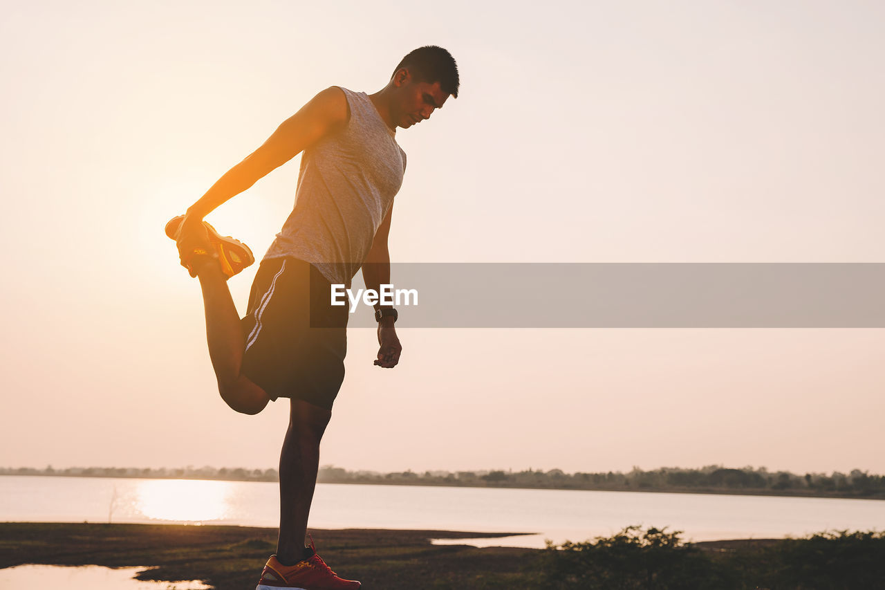 water, one person, sky, lifestyles, sunset, real people, full length, beauty in nature, leisure activity, nature, young adult, lake, men, tranquility, orange color, young men, scenics - nature, standing, outdoors