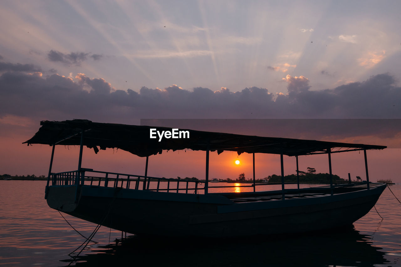 sunset, sky, water, nautical vessel, mode of transportation, transportation, orange color, cloud - sky, beauty in nature, scenics - nature, tranquility, sea, nature, silhouette, waterfront, moored, tranquil scene, no people, idyllic, outdoors, sun, horizon over water, fishing boat