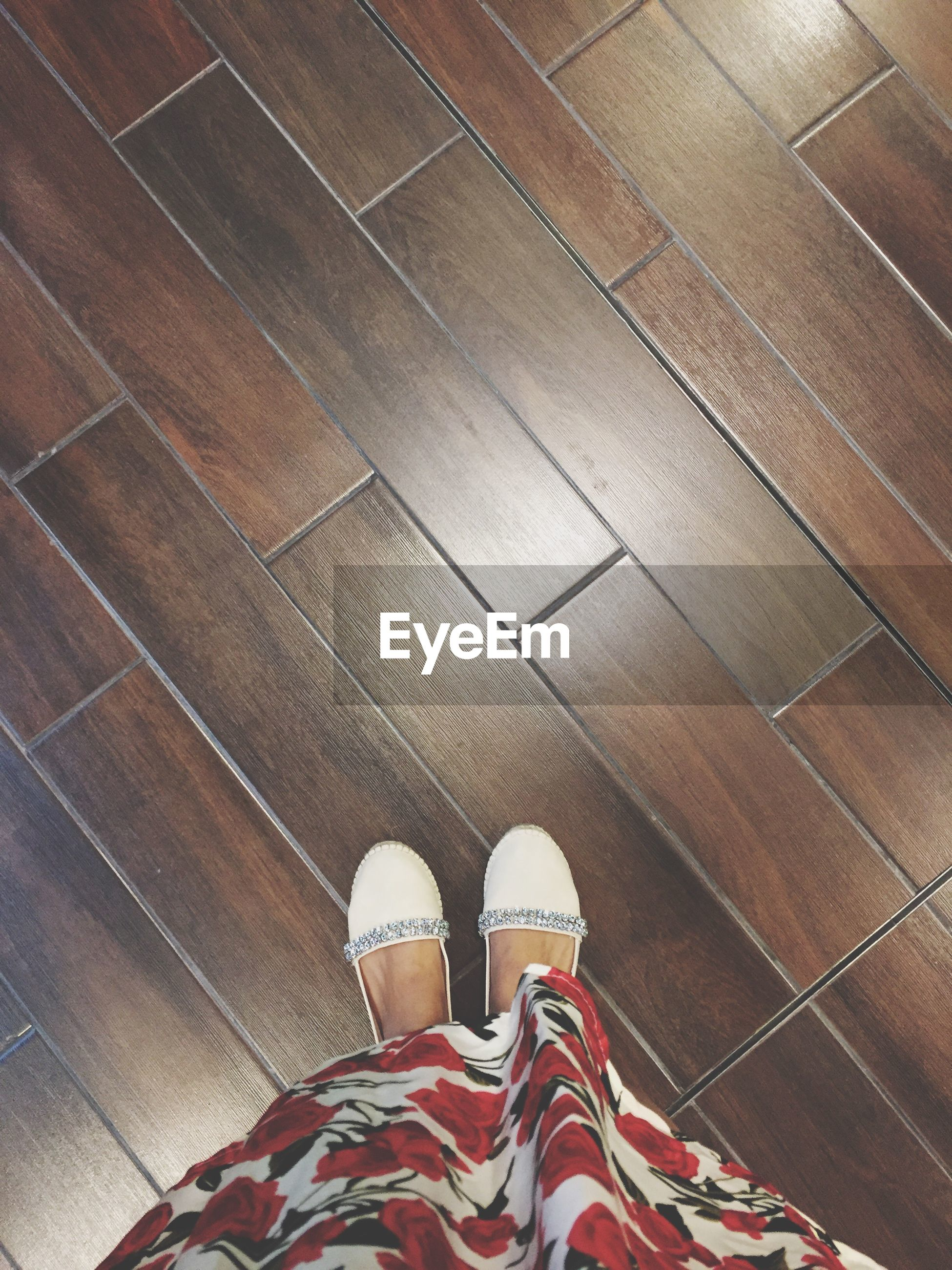 shoe, person, low section, personal perspective, standing, indoors, human foot, wood - material, lifestyles, brown, flooring, high angle view, footwear, wooden, hardwood floor, canvas shoe, sock, day, high section, shoes