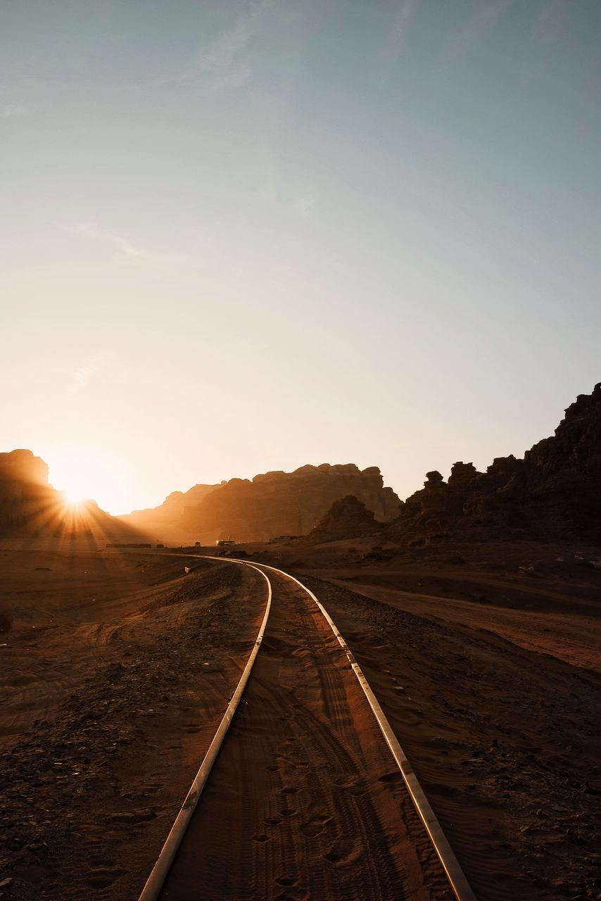 Railroad track against sky during sunset