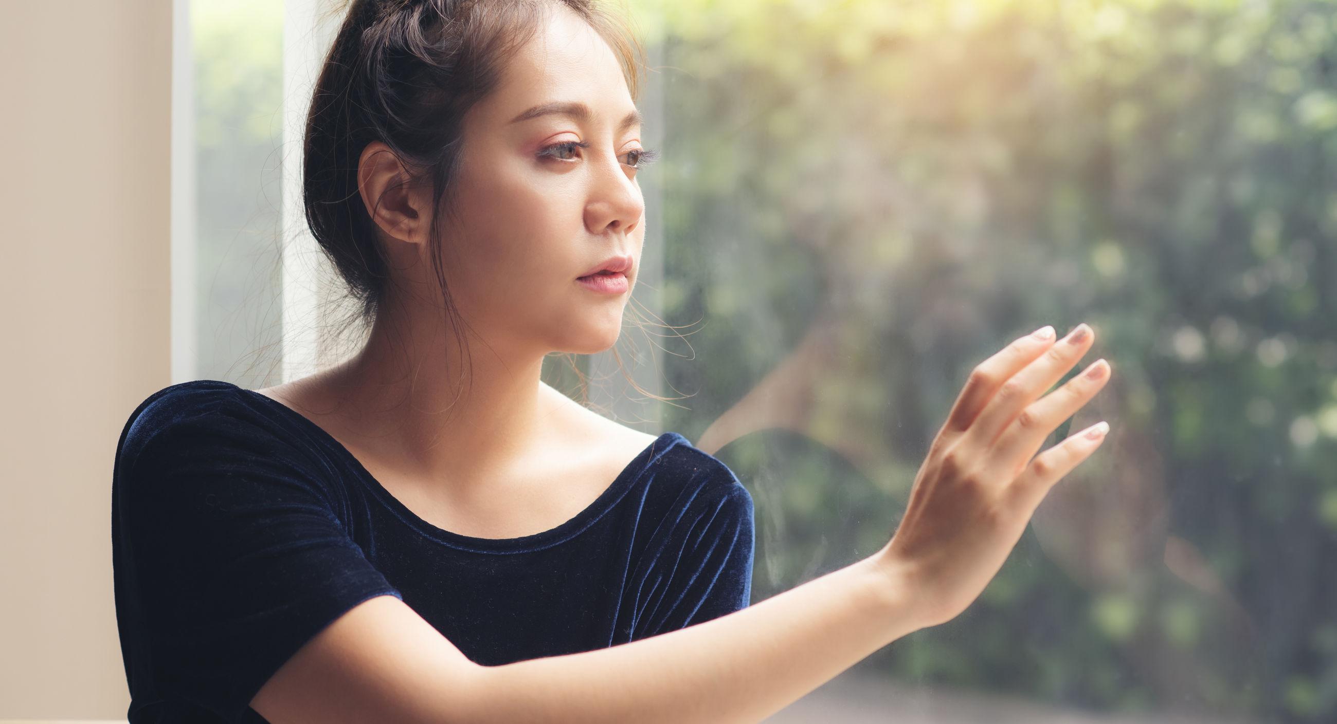 Beautiful young woman looking away through window