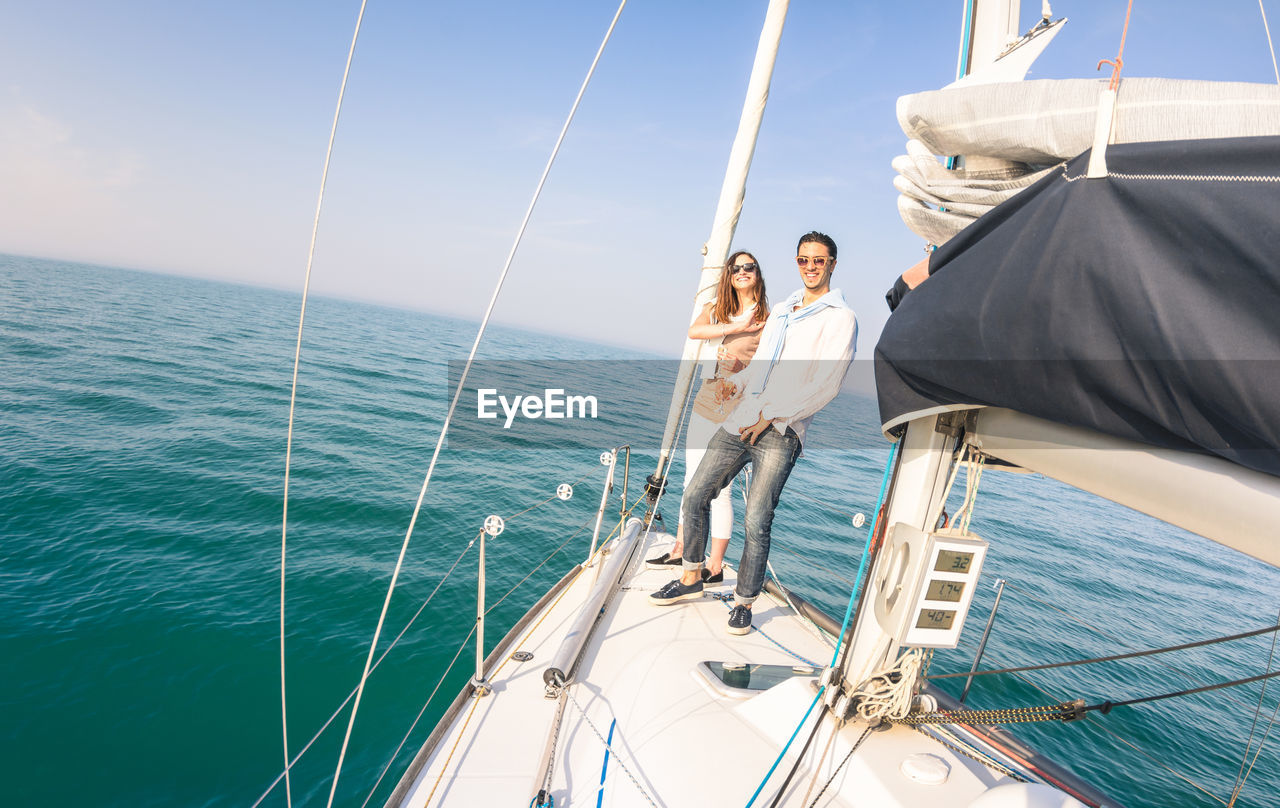 Portrait Of Couple Standing On Boat In Sea Against Sky