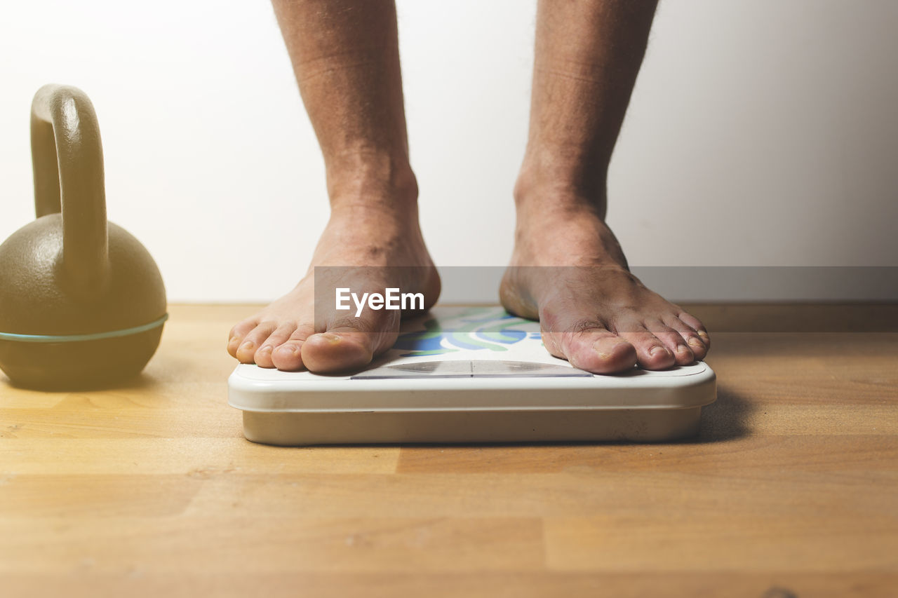 human body part, body part, indoors, one person, low section, human leg, real people, table, barefoot, standing, close-up, human foot, lifestyles, men, wood - material, flooring, adult, weight scale, selective focus, human limb