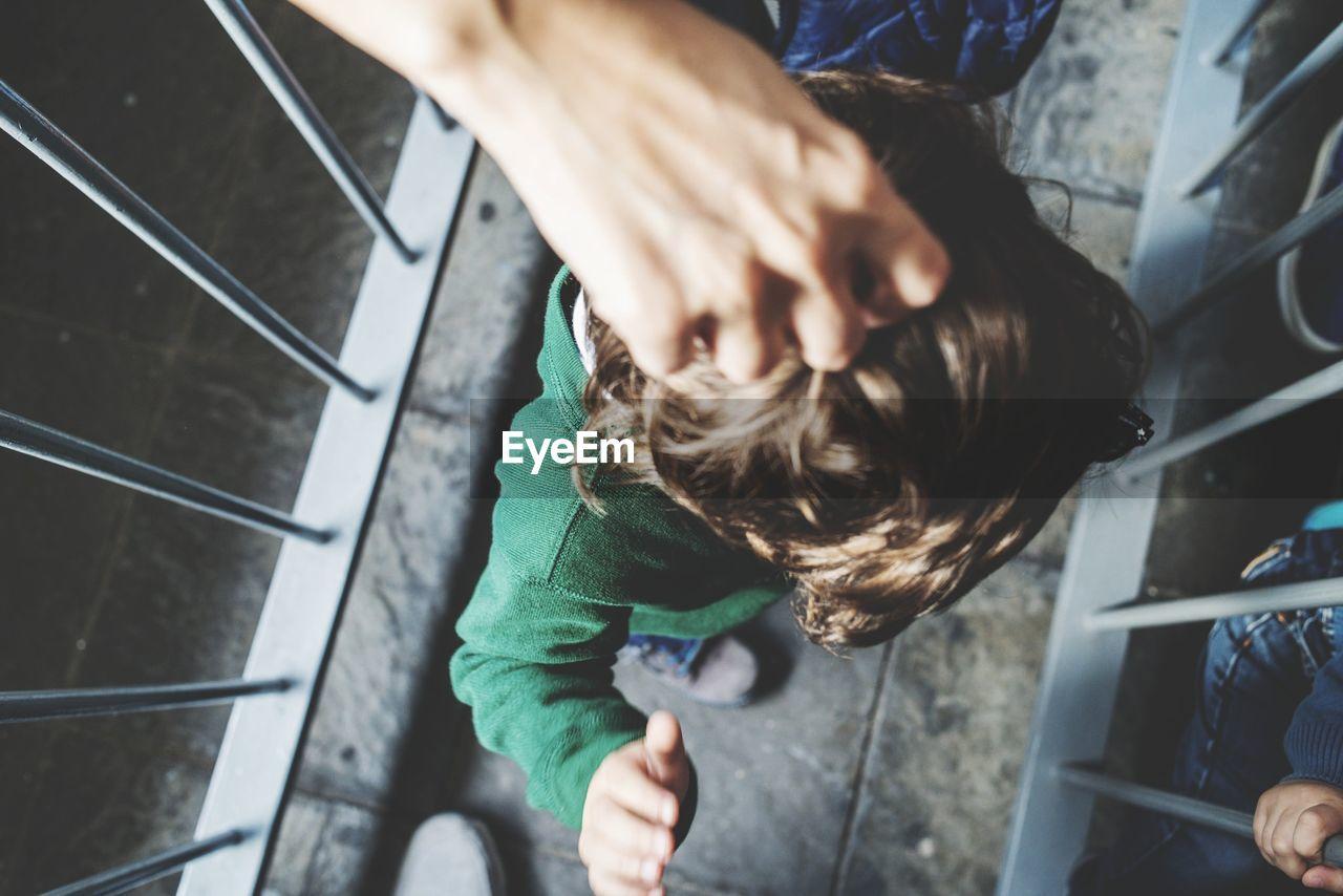 Cropped hand of woman holding boy hair on footbridge
