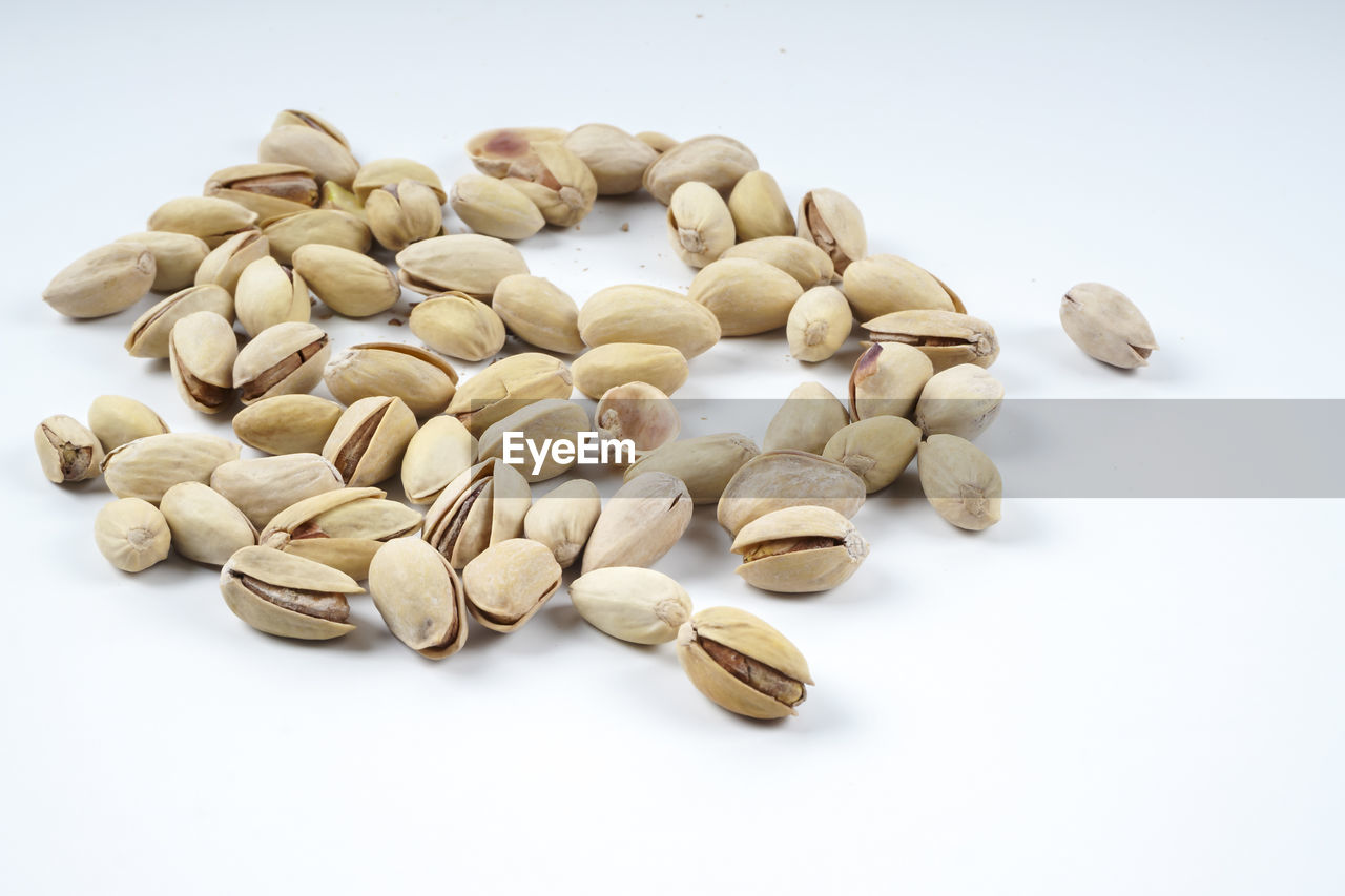 white background, studio shot, food and drink, food, healthy eating, freshness, indoors, no people, still life, wellbeing, large group of objects, close-up, nut, high angle view, raw food, nut - food, copy space, abundance, spice, heap, cardamom, snack