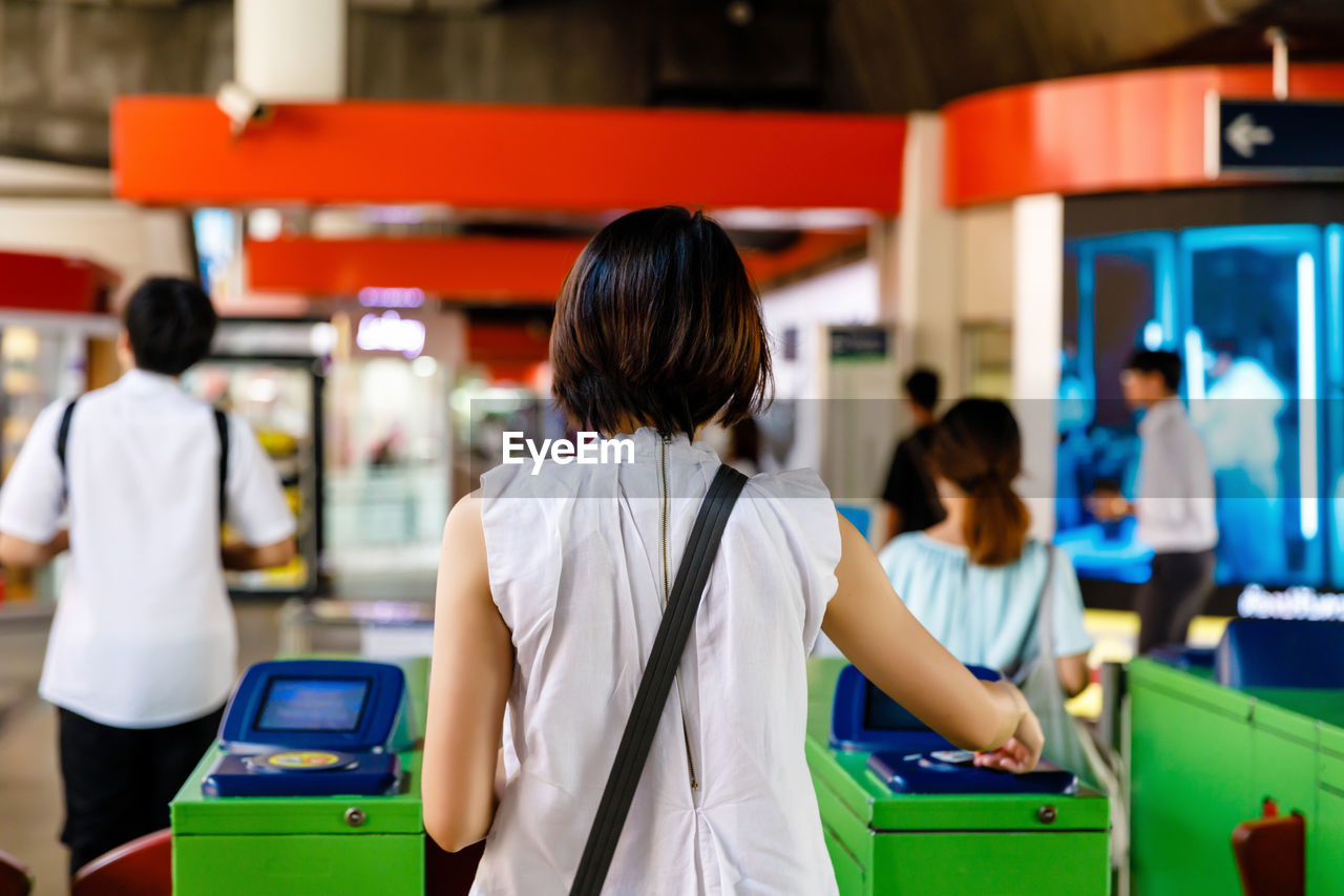 Woman scanning train ticket to entrance gate of sky train or subway, transportation concept