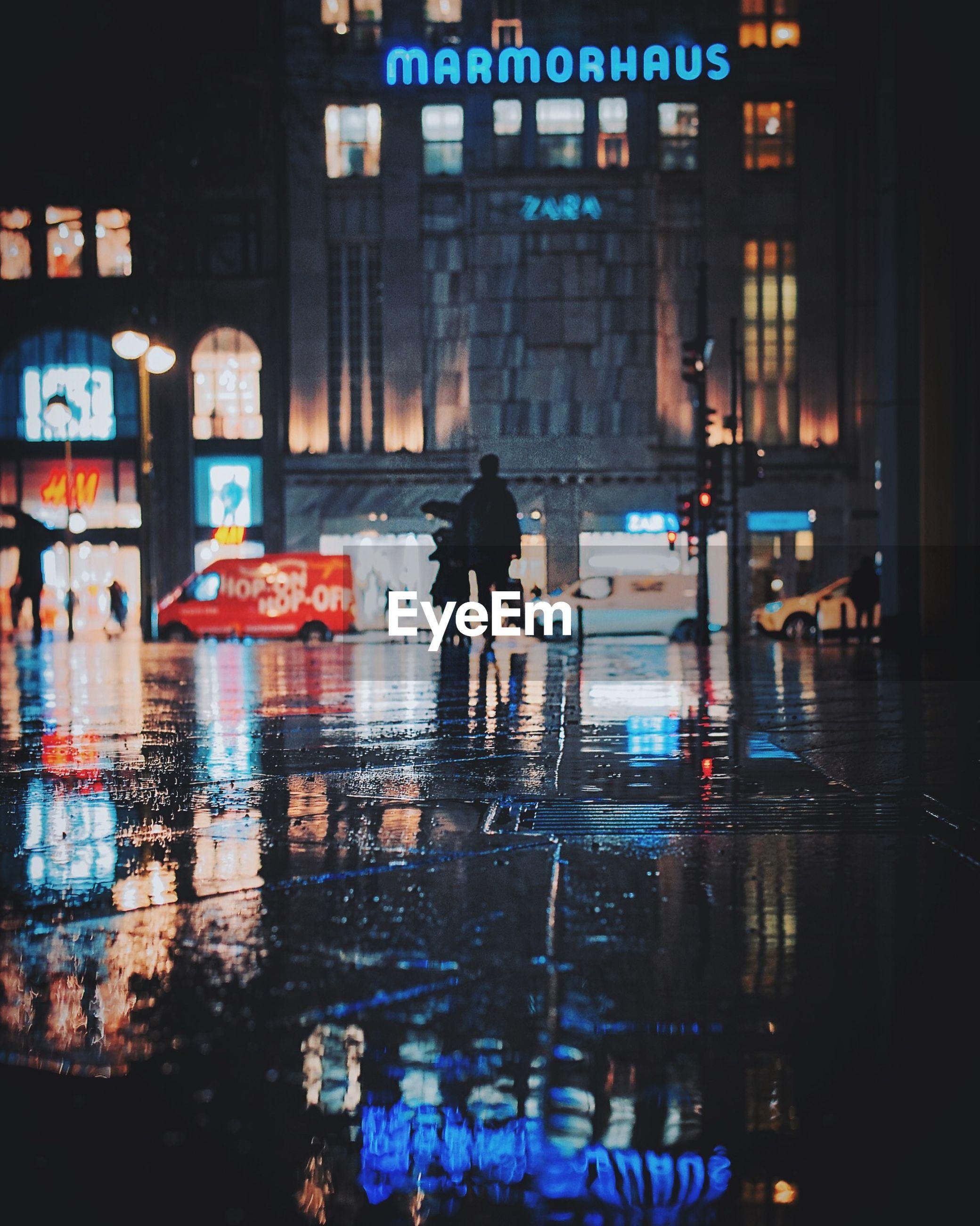 REFLECTION OF MAN WALKING ON WET CITY