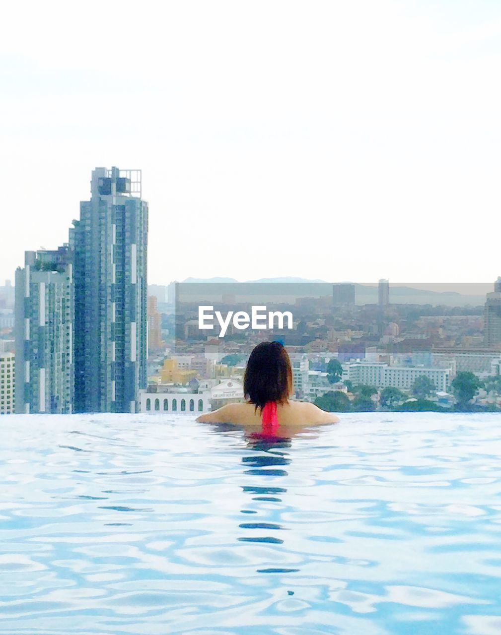 building exterior, built structure, rear view, architecture, one person, city, sky, waterfront, adult, women, building, real people, water, leisure activity, nature, lifestyles, cityscape, day, skyscraper, office building exterior, swimming pool, outdoors, hairstyle, looking at view