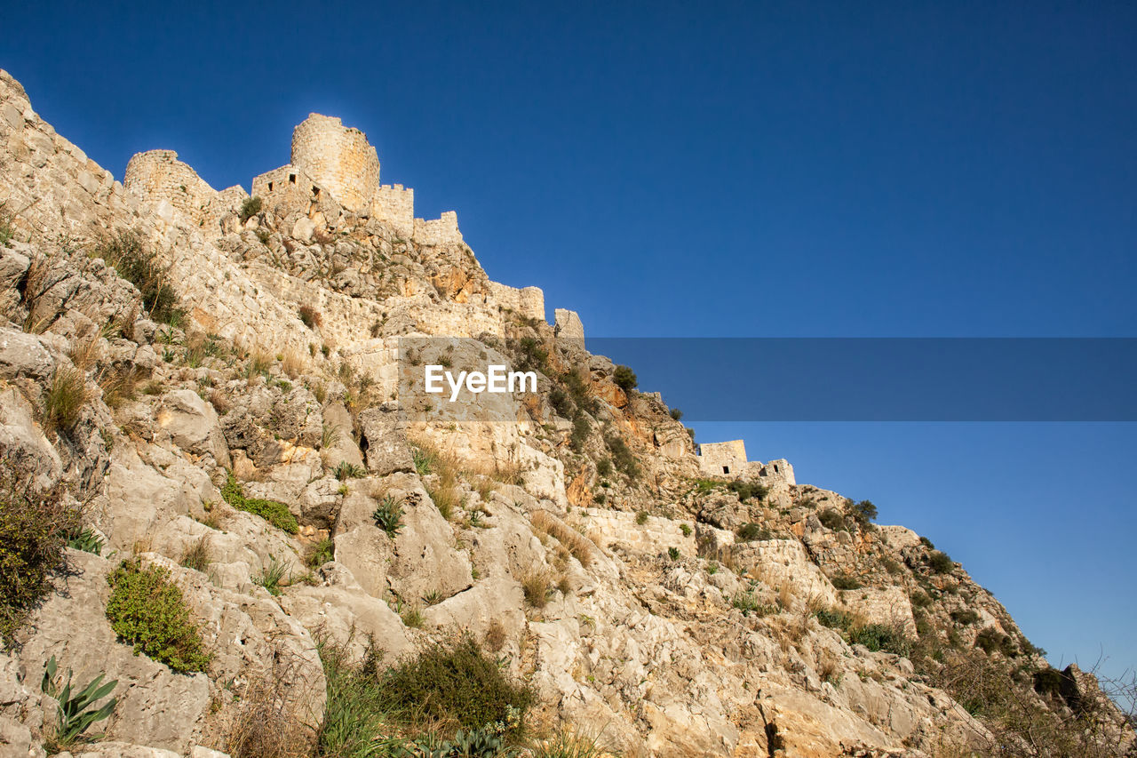 sky, low angle view, clear sky, rock, nature, mountain, rock - object, solid, rock formation, day, beauty in nature, no people, blue, sunlight, architecture, built structure, scenics - nature, history, tranquil scene, tranquility
