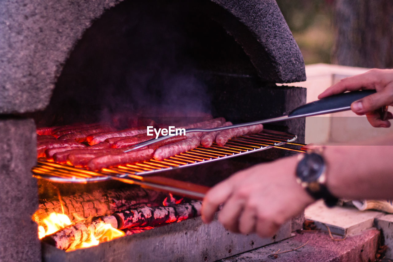 Cropped Image Of Person Hand Cooking Sausages On Barbecue Grill
