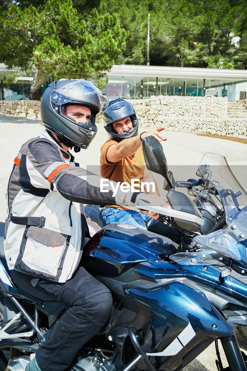 MAN RIDING MOTORCYCLE ON CART