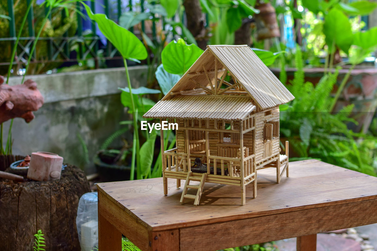 wood - material, day, no people, table, nature, leaf, focus on foreground, plant part, plant, outdoors, birdhouse, green color, seat, growth, architecture, built structure, tree, beauty in nature, craft, absence