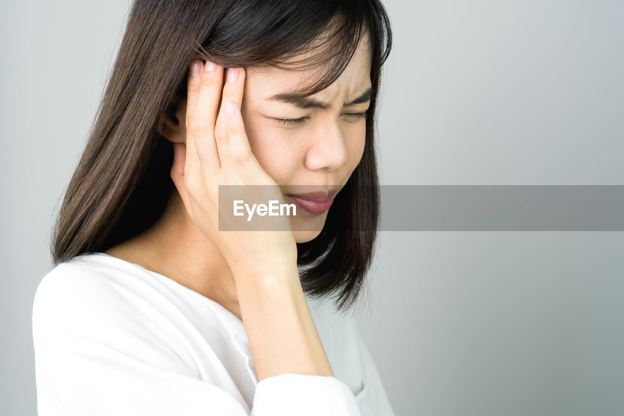 Woman with headache against gray background
