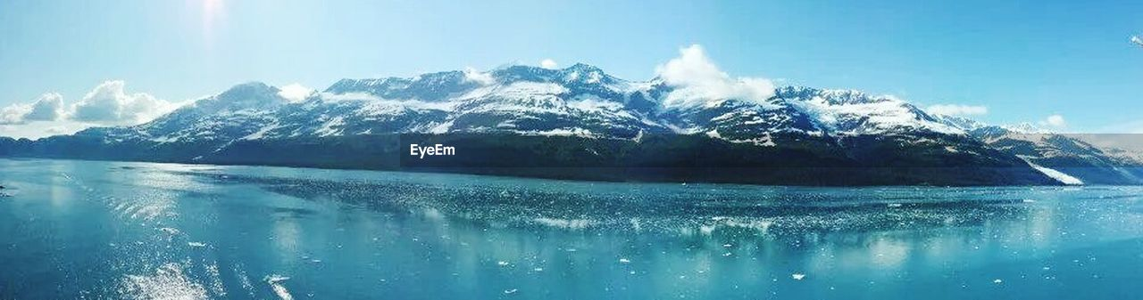 mountain, winter, water, sky, snow, reflection, nature, scenics, cold temperature, blue, sunlight, beauty in nature, outdoors, no people, day, travel destinations, landscape, mountain range, sea, tree, frozen water