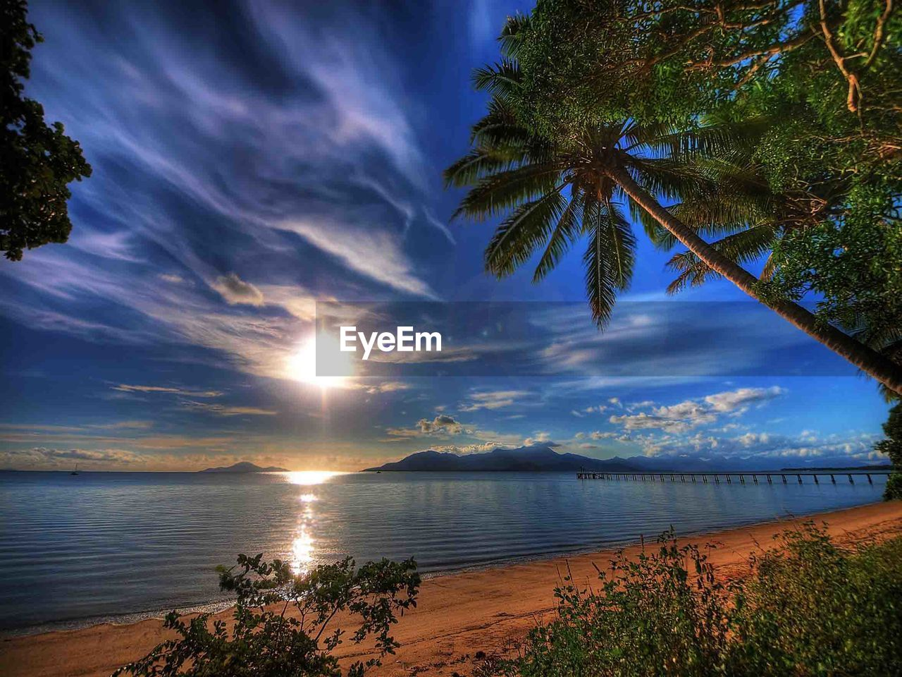 scenics, beauty in nature, tranquil scene, tranquility, sea, palm tree, tree, nature, water, beach, cloud - sky, sky, sunset, idyllic, outdoors, no people, sun, horizon over water, day