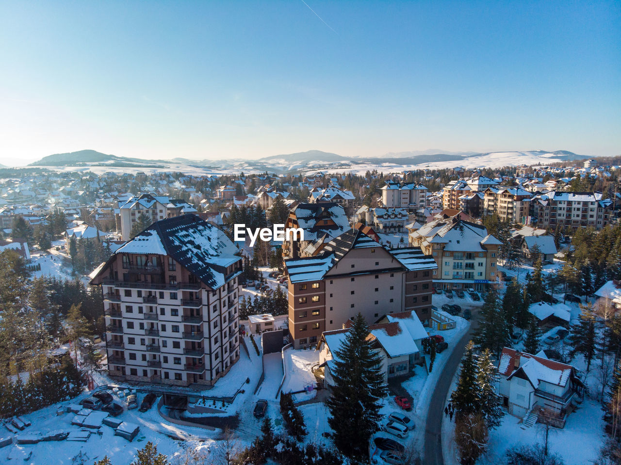 building exterior, architecture, built structure, building, winter, city, snow, residential district, cold temperature, cityscape, sky, nature, crowded, mountain, crowd, high angle view, house, town, outdoors, townscape, snowcapped mountain