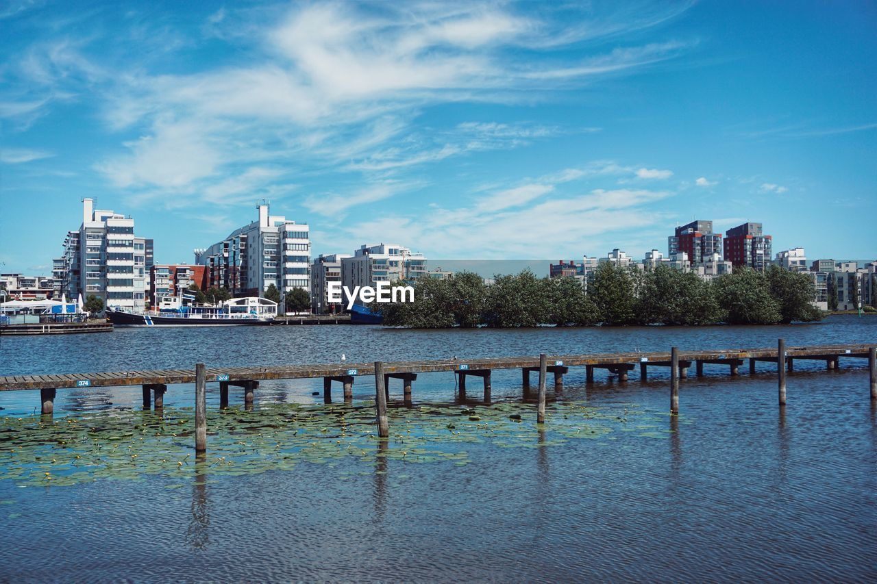 architecture, built structure, building exterior, water, sky, city, waterfront, building, nature, cloud - sky, no people, day, tree, urban skyline, plant, office building exterior, outdoors, river, residential district, cityscape, skyscraper, swimming pool