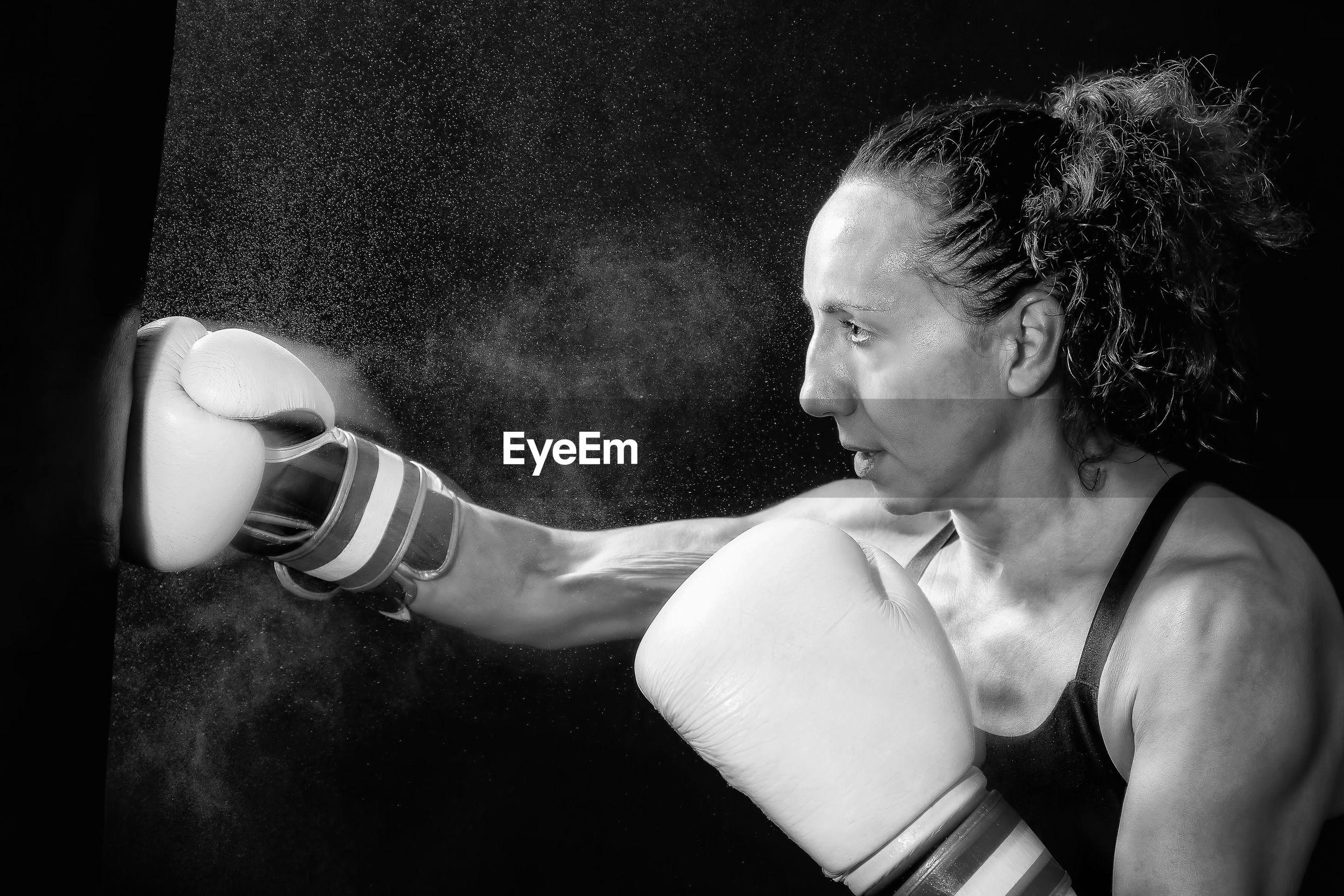 Female boxer punching bag against black background