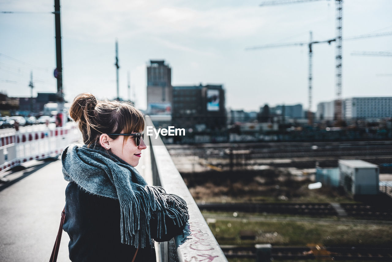 Side View Of Woman On Bridge In City