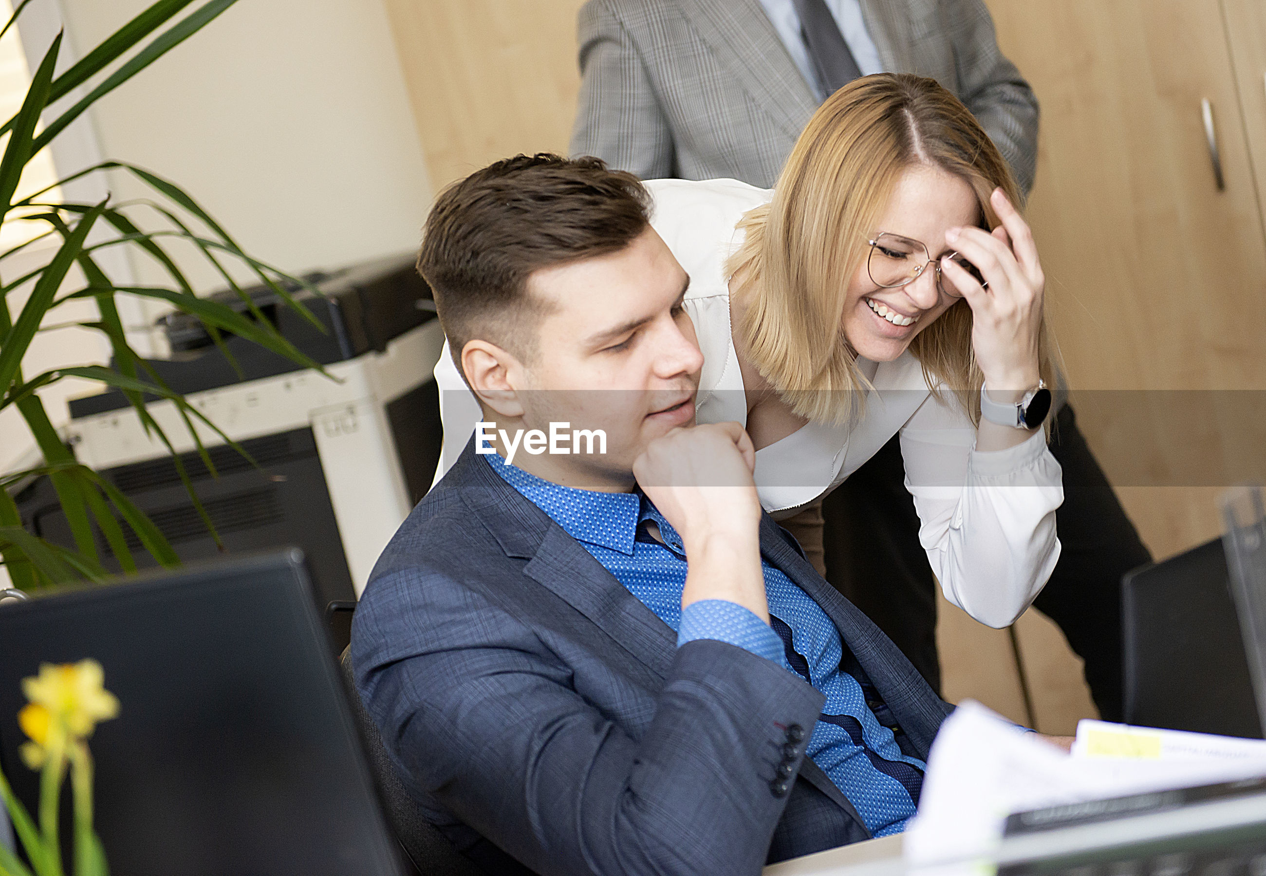Beautiful woman pointing at laptop  and discussing  with her coworker while standing at office