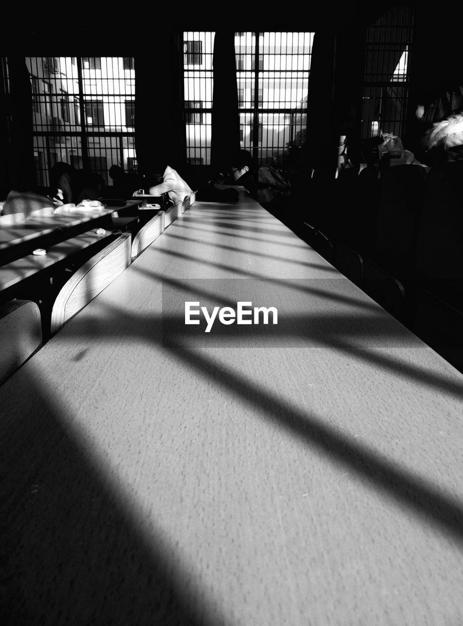 Sunlight Falling On Wooden Desk In Classroom