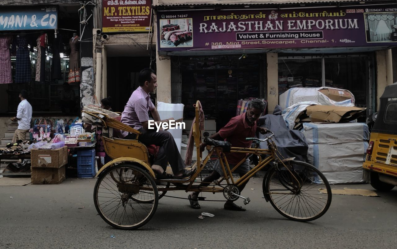 transportation, real people, mode of transportation, text, city, land vehicle, communication, people, street, architecture, men, western script, lifestyles, day, sitting, bicycle, casual clothing, built structure, outdoors
