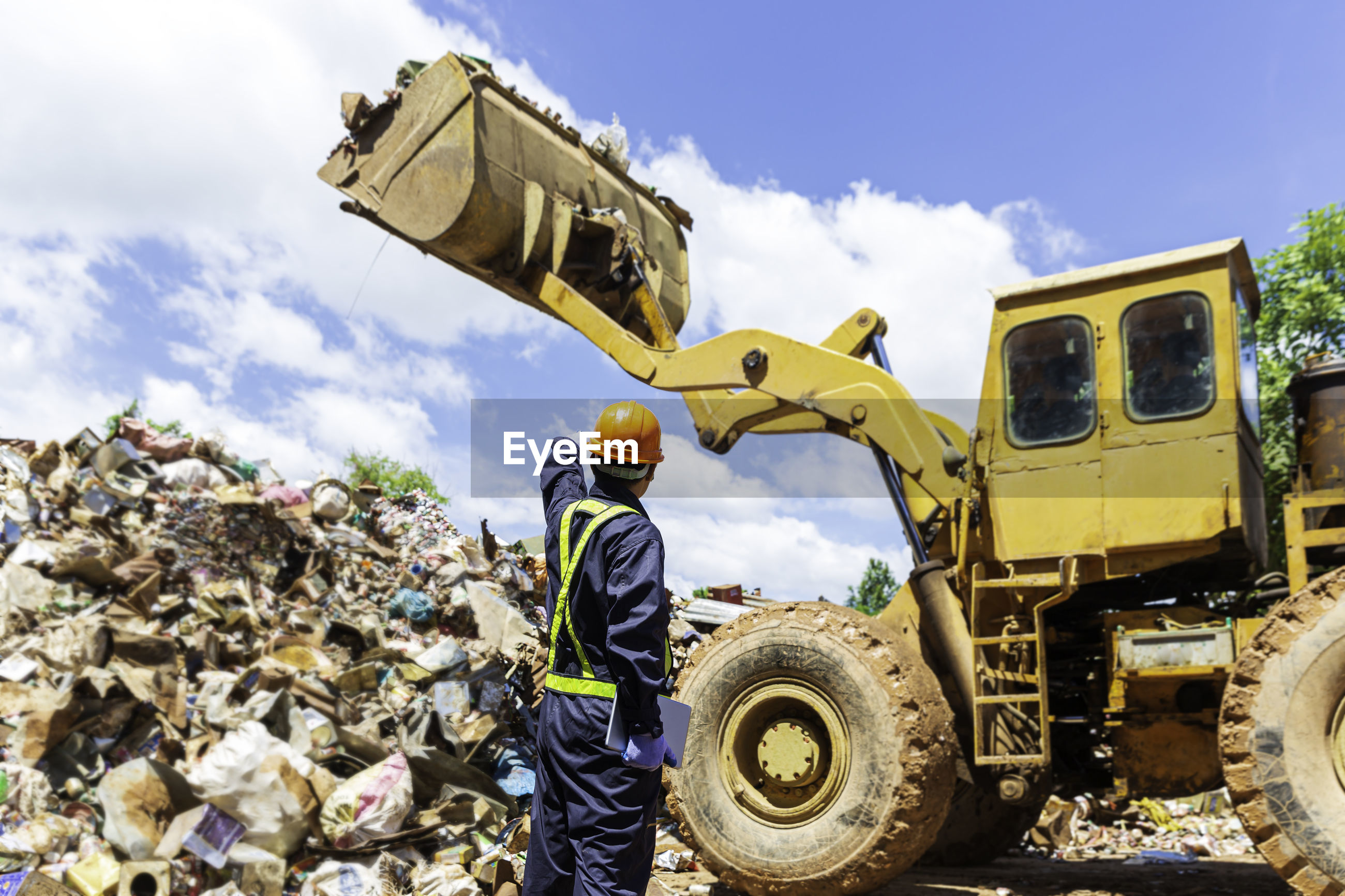 The engineer is controlling the loader to get the iron to recycle. worker standing in metal landfill