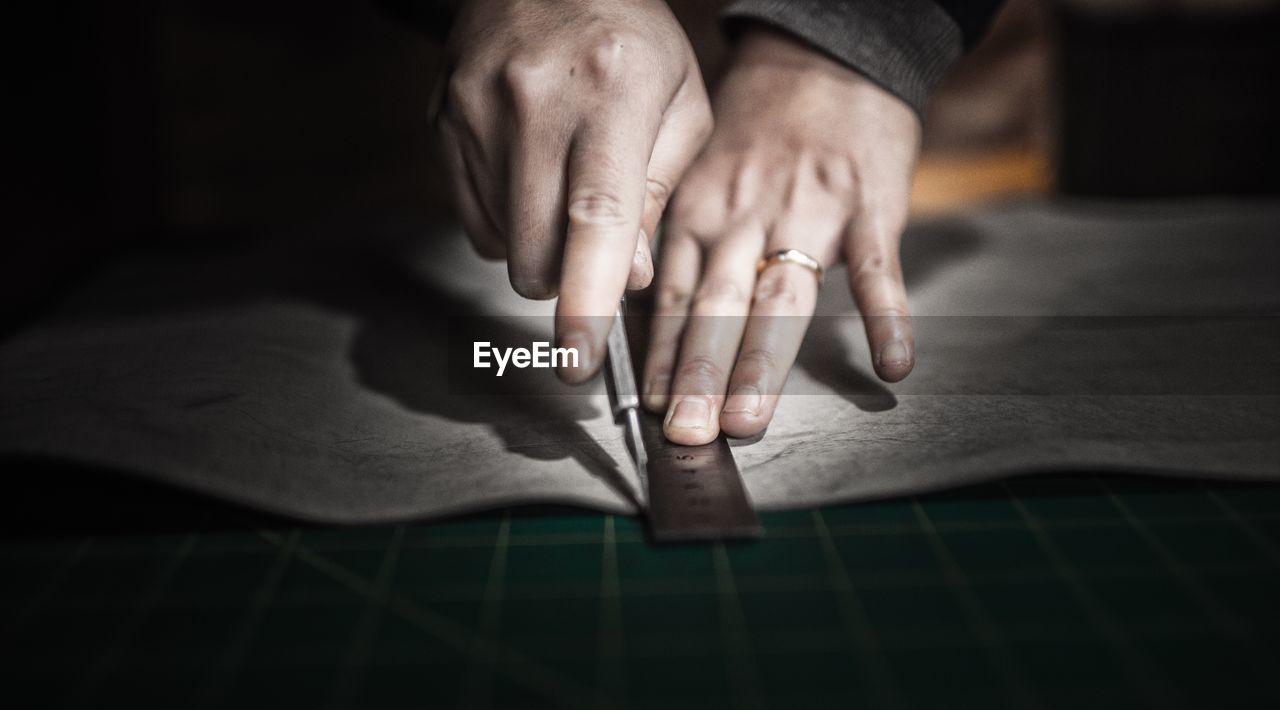 Cropped Image Of Hands Marking On Paper With Ruler